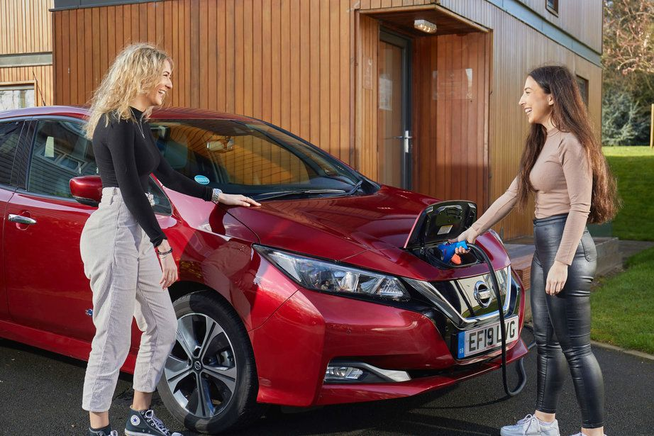 Two women smiling in front of electric vehicle which is being charged