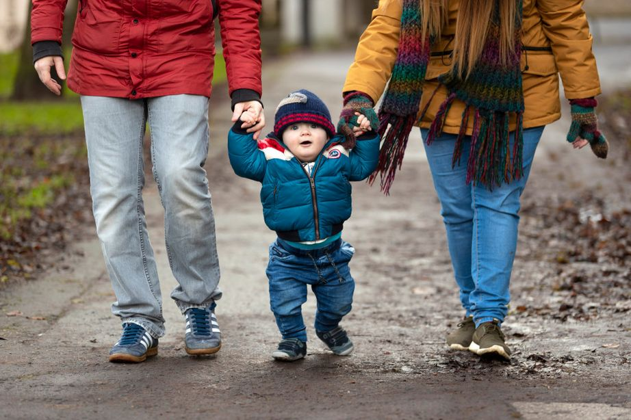 Parents walking and holding hands with toddler in the middle
