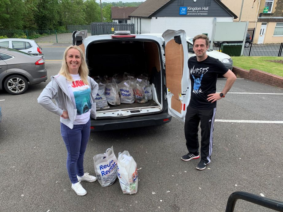 A woman and a man standing outside van with food parcels