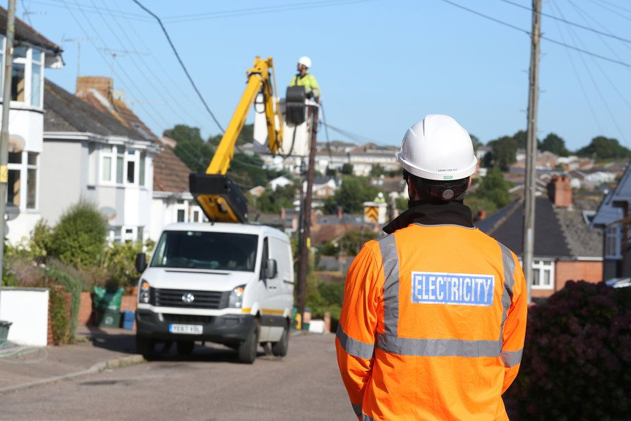 WPD staff replace overhead lines in a suburban street