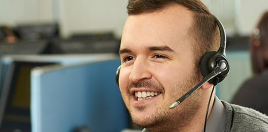 Smiling man taking a call with a headset